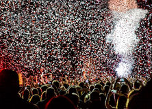 People At An Event. Silhouette of a crowd of people at an event or concert with smoke and clouds of red and white confetti Stock Photos