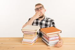 People, exam and education concept - Exhausted and tired student dressed in plaid shirt sitting at the wooden table with. Books stock photo