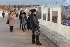 People examine pictures on river Yenisei quay Stock Photos