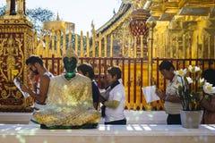 People executing buddhist ritual near Emerald Buddha Statue. Royalty Free Stock Image