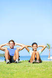 People exercising - Couple doing sit ups outdoors. Fitness couple doing situps exercise during outside cross training workout. Happy young multiracial couple Royalty Free Stock Image