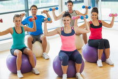 People exercising with dumbbells on fitness balls Royalty Free Stock Photos