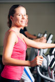 People exercising on elliptical trainer in gym Royalty Free Stock Photos