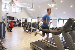 People exercising in a gym, blurred man runs in foreground Royalty Free Stock Photo