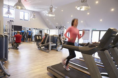 People exercising in a gym, blurred woman runs in foreground Royalty Free Stock Images