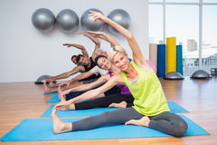 People exercising on mats in fitness club stock image