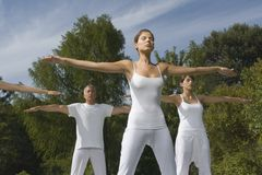 3 people exercising in a park stock image