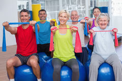 People exercising with resistance bands in gym class. Portrait of happy people on fitness balls exercising with resistance bands in gym class Stock Images