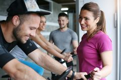 People exercising on stationary bikes in fitness class. stock image