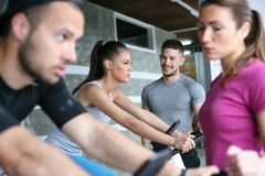 People exercising on stationary bikes in fitness class. stock photo