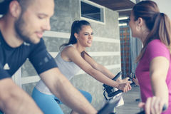 People exercising on stationary bikes in fitness class. People workout in gym. People with personal trainer Stock Images