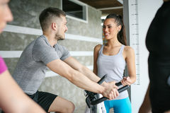 People exercising on stationary bikes in fitness class. People workout in gym. People with personal trainer Stock Photos