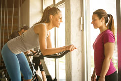 People exercising on stationary bikes in fitness class. People workout in gym. Personal trainer helping young woman. Focus on two women Royalty Free Stock Photography