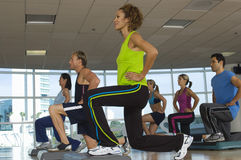 People Exercising On Step In Aerobics Class Stock Images