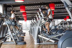 People exercizing in row of treadmills. AMERSFOORT, THE NETHERLANDS - SEPTEMBER 13, 2014: Active people exercizing in a row of cross trainers at a sports gym in Stock Photography