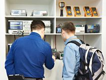 People on exhibition of electronic measuring devices. Of voltmeters and oscillographs royalty free stock image