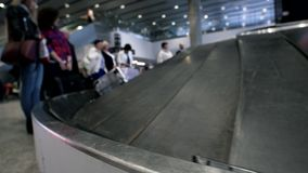 People expect their luggage on the conveyor belt at the airport. Blured stock footage