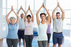 People with eyes closed and joined hands at fitness studio Stock Photo