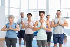 People with eyes closed and joined hands at fitness studio Royalty Free Stock Photo