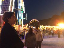 People at a fair watching others on a fun ride. Fair, carousels, Big Whil lighted at night Stock Photo