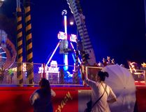 People at a fair watching others on a fun ride, waving. Fair, carousels, Big Whil lighted at night Stock Photos
