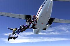 People falling from airplane. Group of skydiver's exit L410 Turbolet in formation with blue sky and cirrus clouds from 13000 feet. Freefall and freedom of flight royalty free stock photo
