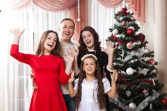 People family, christmas and adoption concept - happy mother, father and children hugging near a Christmas tree at home Royalty Free Stock Photos