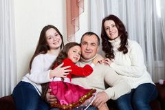 People family, christmas and adoption concept - happy mother, father and children hugging near a Christmas tree at home. Christmas family portrait royalty free stock images