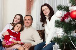 People family, christmas and adoption concept - happy mother, father and children hugging near a Christmas tree at home. Christmas family portrait stock photos