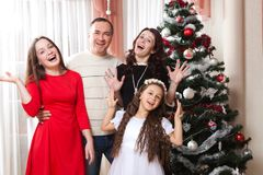 People family, christmas and adoption concept - happy mother, father and children hugging near a Christmas tree at home Stock Photos