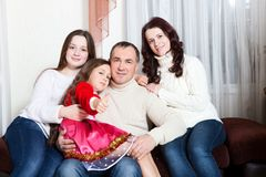 People family, christmas and adoption concept - happy mother, father and children hugging near a Christmas tree at home royalty free stock images