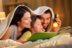 Happy family reading book in bed at night at home. People and family concept - happy mother, father and little daughter reading book with torch light in bed Royalty Free Stock Photo