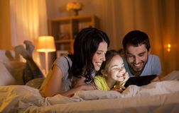 Family with tablet pc in bed at night at home stock photos