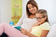 Happy girl with mother reading book at home stock images
