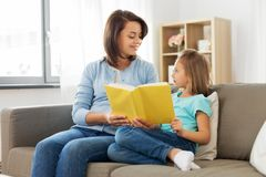 Happy girl with mother reading book at home stock photos
