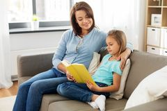 Happy girl with mother reading book at home royalty free stock photography