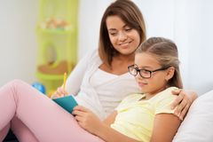 Happy girl with mother writing to notebook at home royalty free stock photography