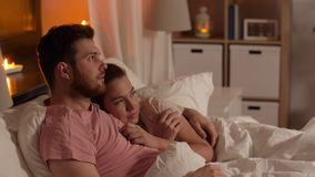 Couple watching horror on tv in bed at night. People, family and leisure concept - happy couple watching tv in bed at night at home stock footage
