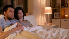 Scared couple watching horror movie on tv at home stock footage