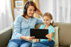 Mother and daughter listen to music on tablet pc stock photos