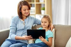 Happy mother and daughter with tablet pc at home stock images