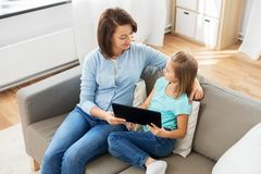 Happy mother and daughter with tablet pc at home stock photography