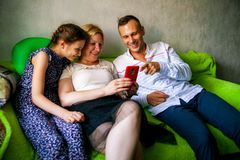 Happy mother, father and little girl with smartphone in bed at home. stock images