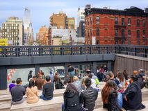 People in the famous High Line Park in New York. New York, USA, november 5, 2016: people looking out onto the New York City streets through one of the Royalty Free Stock Image