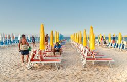 People on the famous San Vito Lo Capo beach among of closed umbrellas and sunbeds at the end of the day. Stock Photos