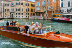 People in fancy dress ride on Grand Canal, Venice. Venice, Italy - May 23, 2015: Happy people in fancy dress ride on a boat on the Grand Canal Stock Image