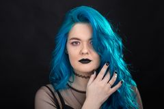 People and fashion concept - Young and attractive woman with black lipstick and blue hair posing over black background royalty free stock photo