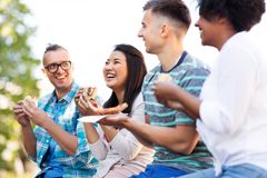 Happy friends eating sandwiches and pizza outdoors royalty free stock images