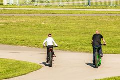 People on fat bicycles skate on a track on a sunny spring day.  Stock Photography