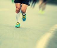 People feet on city road in marathon running race Stock Photos